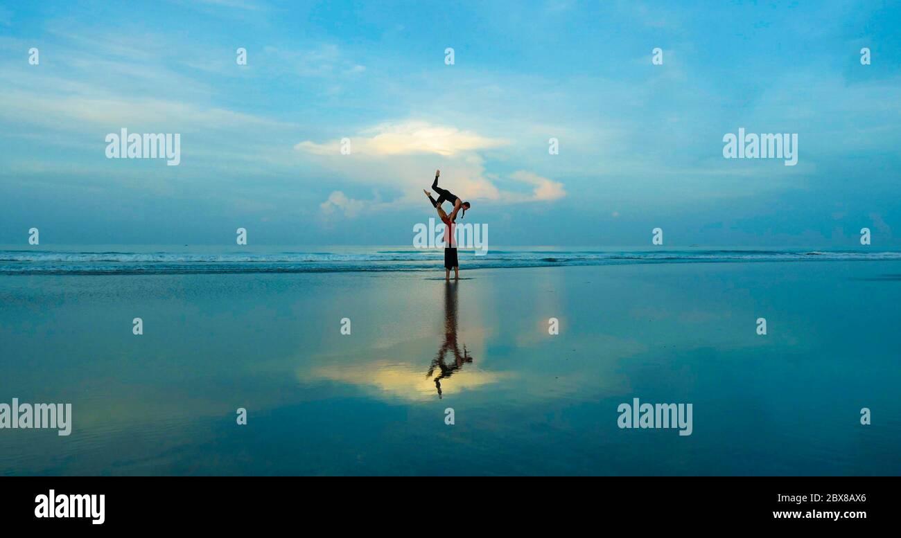 sano y atractivo ajuste pareja de acróbatas haciendo el equilibrio de la acroyoga y ejercicio de meditación en la hermosa playa del desierto practicando el equilibrio y la armonía Foto de stock