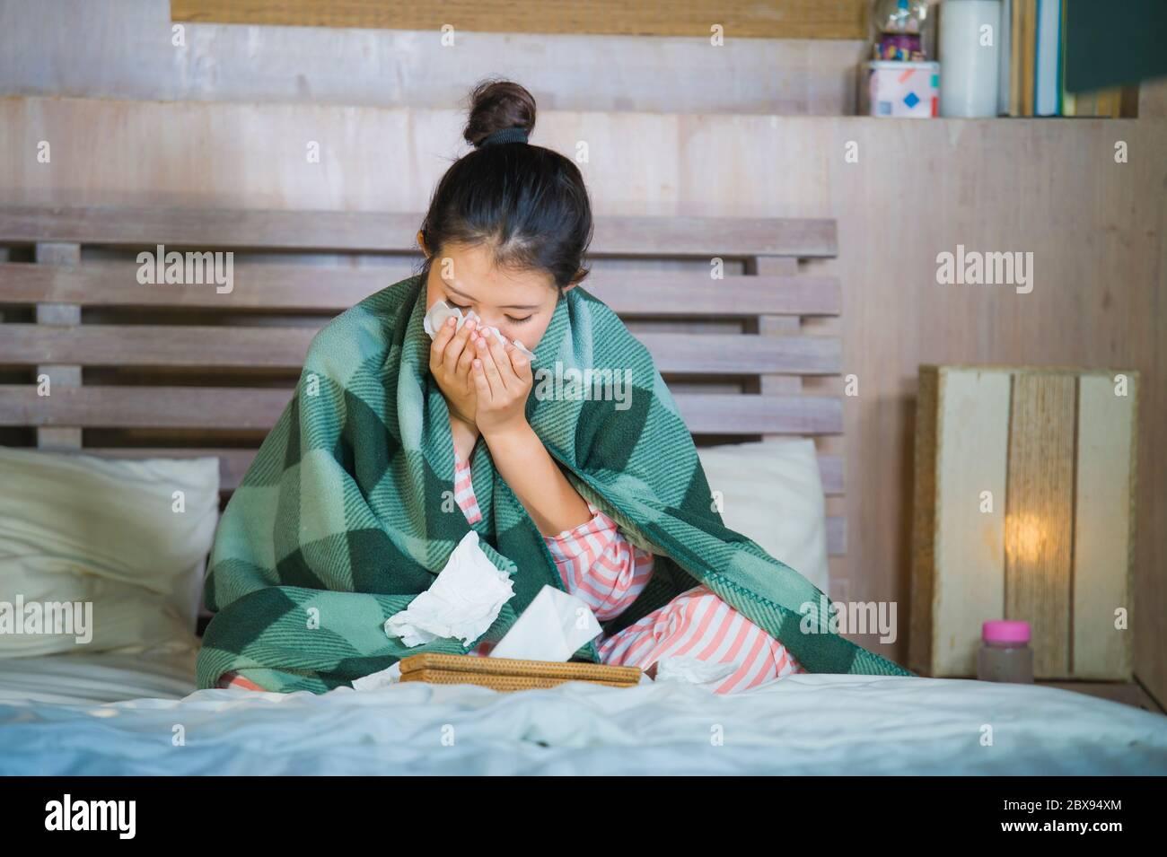 Joven hermosa y dulce niña coreana asiática en pijama enfermo en el dormitorio de casa que sufre de frío y gripe tomar la temperatura con termómetro en la cama soplando Foto de stock