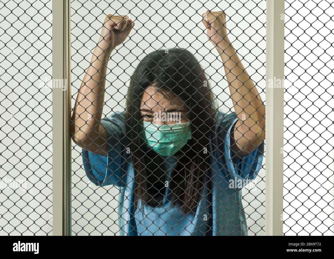 Retrato dramático de una joven China asiática infectada con virus víctima de enfermedades contagiosas o paciente psicótico e insano mental encerrado en el seur Foto de stock