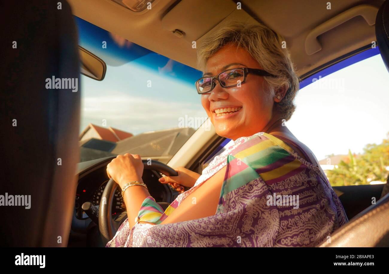 estilo de vida Retrato de verano de mediana edad feliz y atractiva clase asiática Indonesia conducir coche de la mano izquierda sonriendo alegre y libre en un soleado Foto de stock