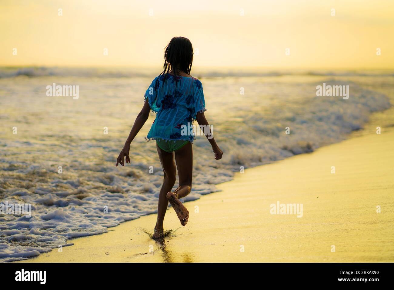 Espalda seguimiento gimbal tiro a pie de 7 u 8 años de edad Indonesia asiática niña corriendo feliz en la hermosa playa disfrutando de vacaciones de verano en childho Foto de stock