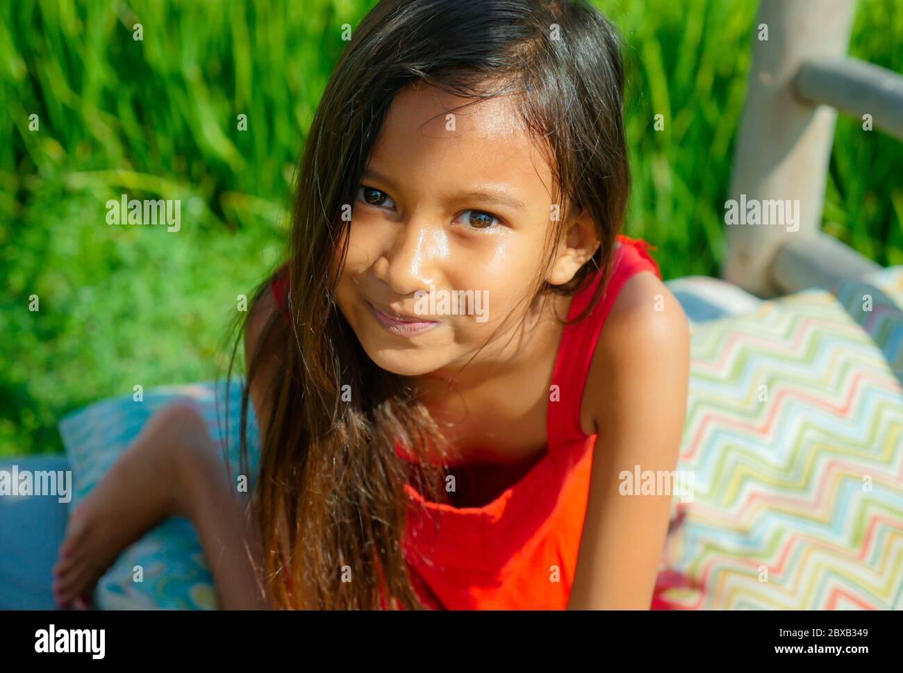 estilo de vida al aire libre retrato de hermosa y dulce niña sonriendo feliz y alegre el niño con ojos preciosos y vestido con un vestido rojo isola Foto de stock