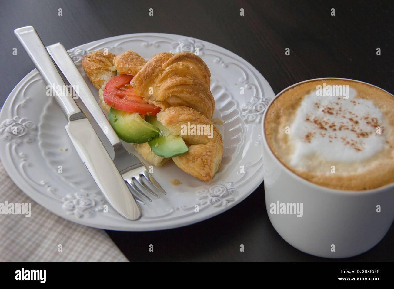 Croissant fresco relleno de aguacate y tomate, una taza de capuchino en una mesa oscura, luz de la mañana desde la ventana Foto de stock