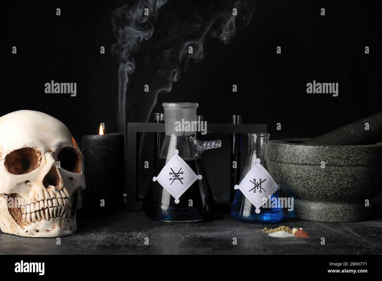 Pociones, cráneo humano, mortero y pedrería en la mesa del alquimista Foto de stock
