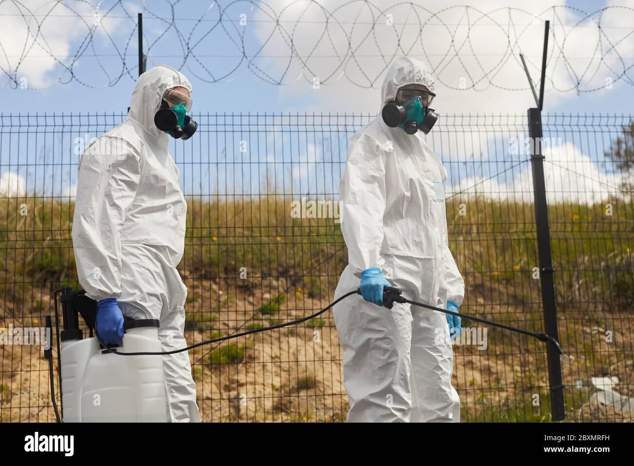 Retrato de dos trabajadores que usan equipo de protección y productos químicos de pulverización al aire libre, parados por una valla de alambre de púas durante la desinfección o limpieza en milígulo Foto de stock