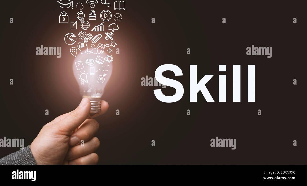 Concepto de habilidad. Resumen bombilla luminosa en las manos, los símbolos de conocimiento, cualificación y experiencia salen de ella Foto de stock