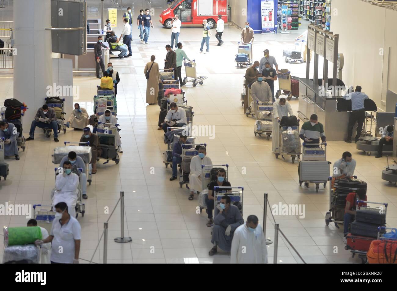 Gobernación de Farwaniya, Kuwait. 8 de junio de 2020. Pasajeros egipcios esperan en la sala de salida del Aeropuerto Internacional de Kuwait durante una operación de repatriación en la provincia de Farwaniya, Kuwait, 8 de junio de 2020. Kuwait planea reanudar los vuelos comerciales en tres etapas, dijo el domingo el Ministro de Estado de Asuntos de Servicios y el Ministro de Estado de Asuntos de la Asamblea Nacional Mubarak al-Harees. Cabe señalar que el aeropuerto de Kuwait ha estado trabajando conjuntamente con los ministerios pertinentes para repatriar a residentes extranjeros que esperan volver a casa, dijo el ministro. El 13 de marzo, Kuwait suspe crédito: Xin Foto de stock