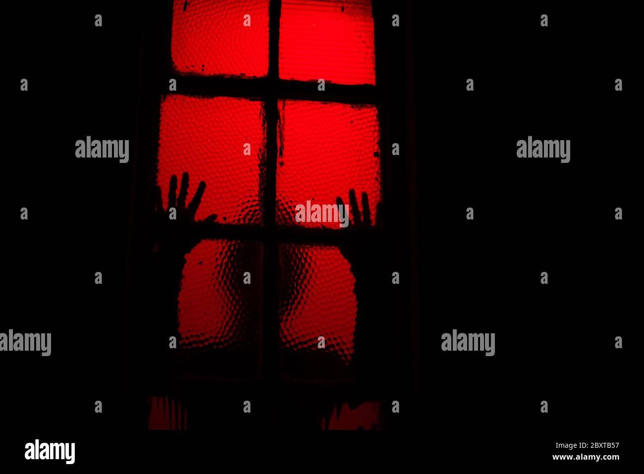 Una sihouette de miedo de la persona que se inclina contra la ventana en la oscuridad Foto de stock