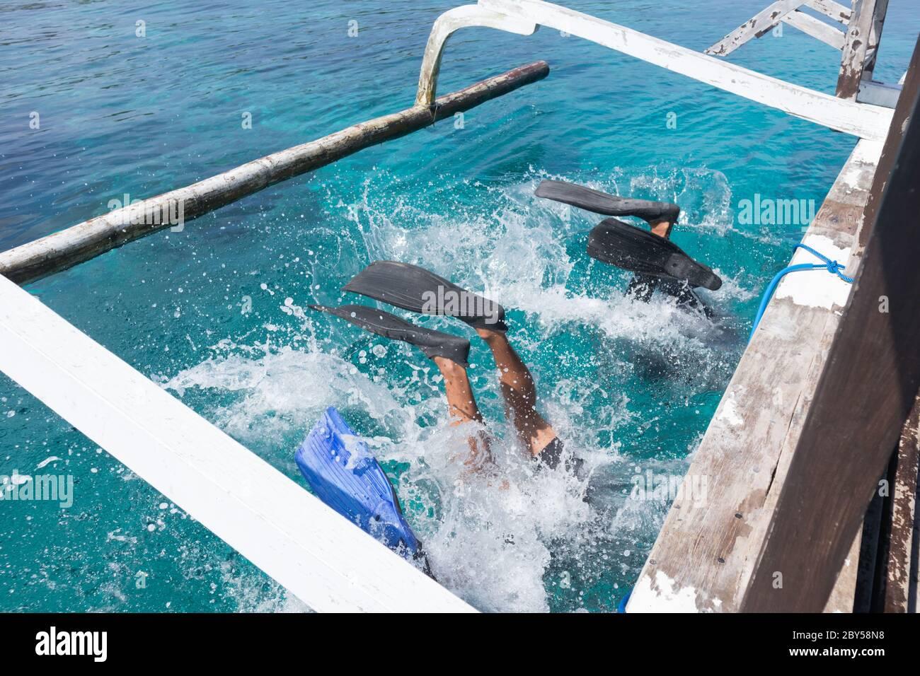 Los buceadores que hacen atrás se voltean al mar azul transparente desde el tablero de un barco. Hay varias maneras de bajar del barco cuando se bucea. Uno de ellos ya está Foto de stock