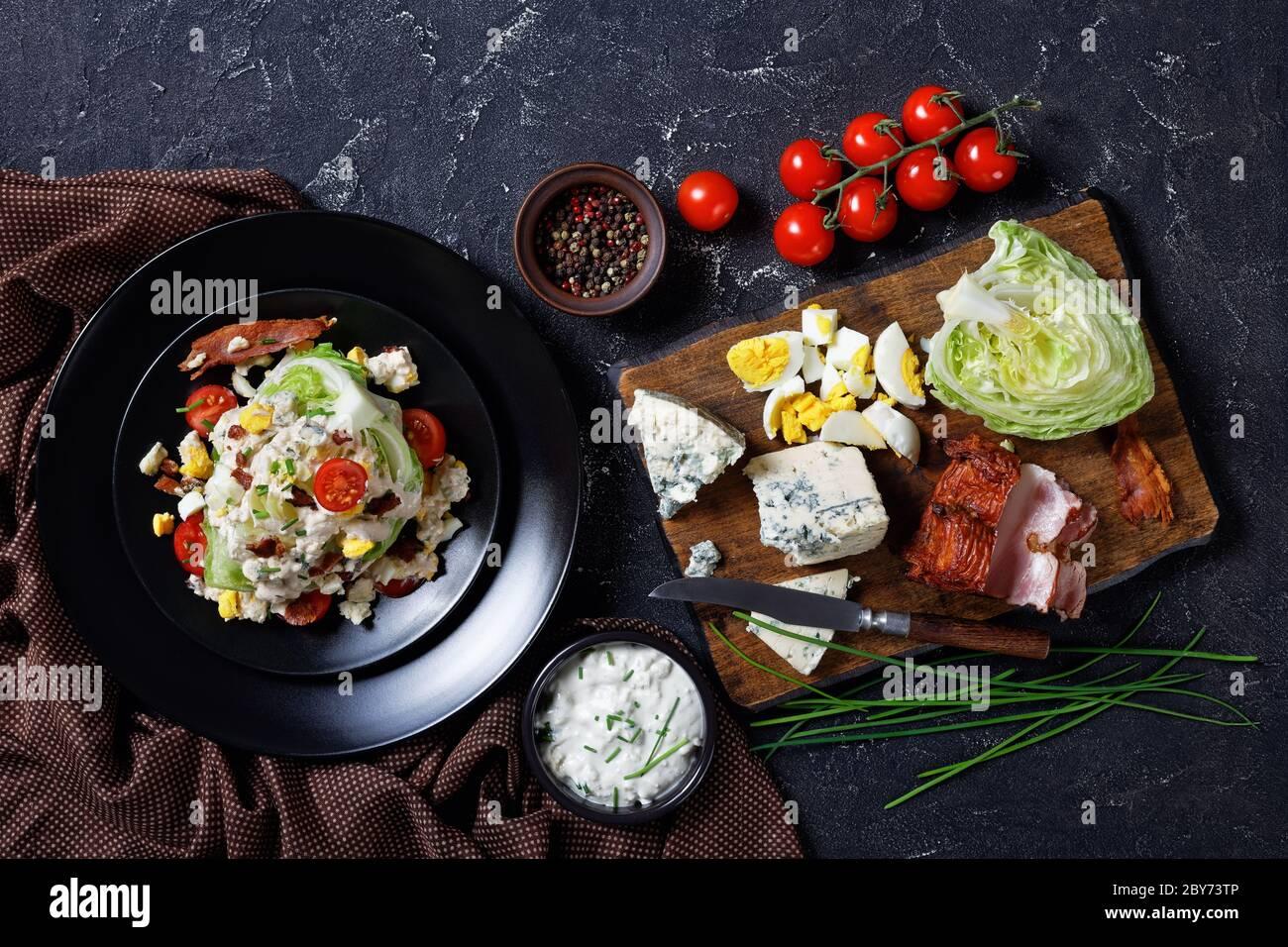 ensalada de cuña de iceberg cubierta con aderezo de queso azul, tocino frito crujiente, tomates cherry, huevos duros desmenuzados, cebolletas en platos negros en un conc Foto de stock