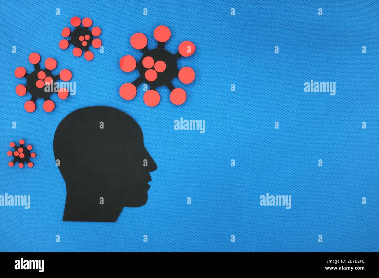 Concepto de depresión y ansiedad pandémica de la salud mental Covid-19. Perfil de cabeza humana de silueta masculina con coronavirus en fondo azul con espacio de copia. Foto de stock