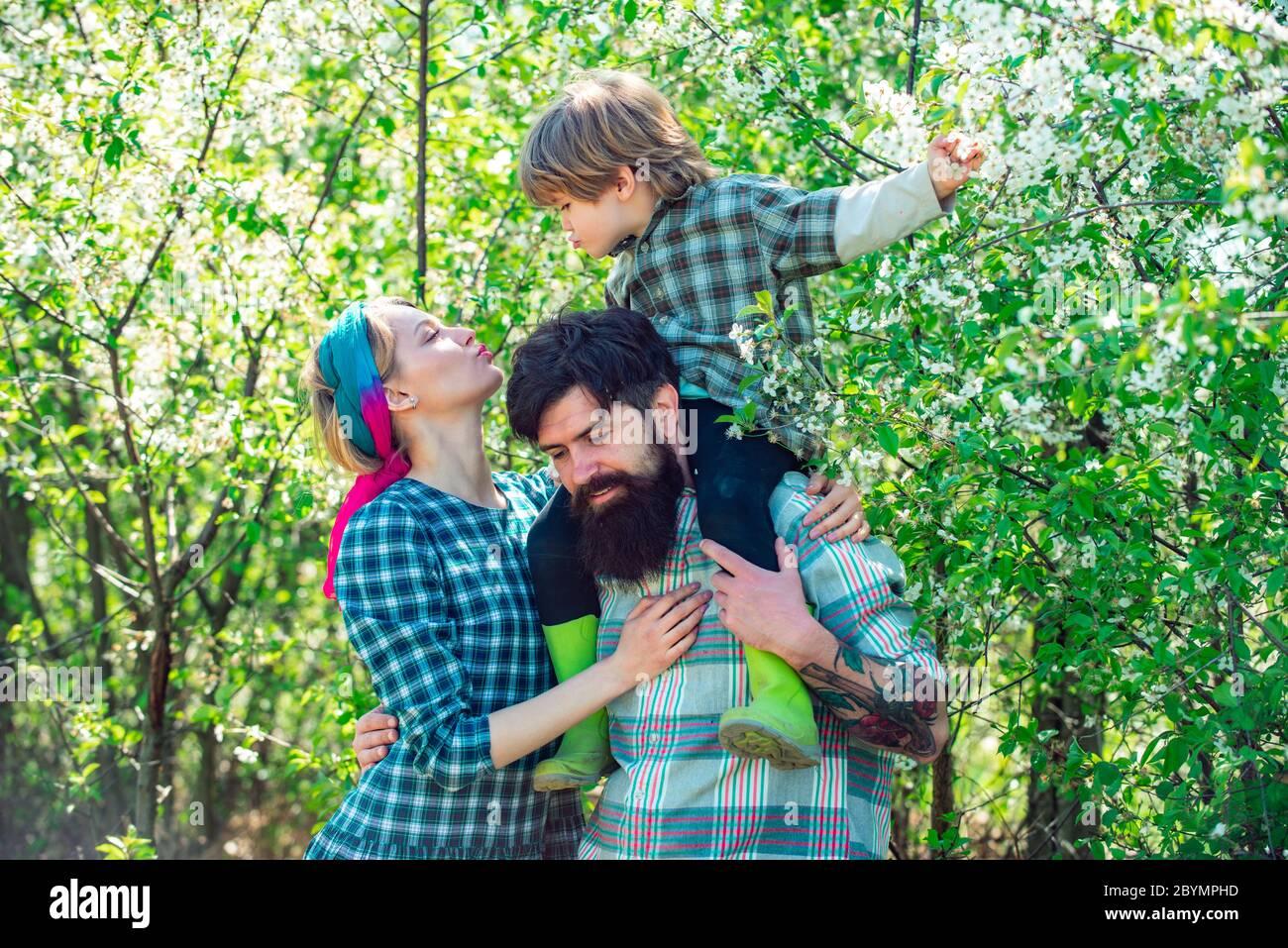Familia caminando juntos por el campo de flores de primavera. Familia feliz pasando tiempo juntos en el jardín. Familia caminando en el campo agrícola. Foto de stock