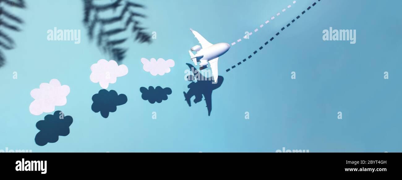 El avión blanco está volando a través del océano. Detrás de él hay nubes y palmeras. Concepto de restauración de vuelos después de la cuarentena y la apertura de fronteras Foto de stock