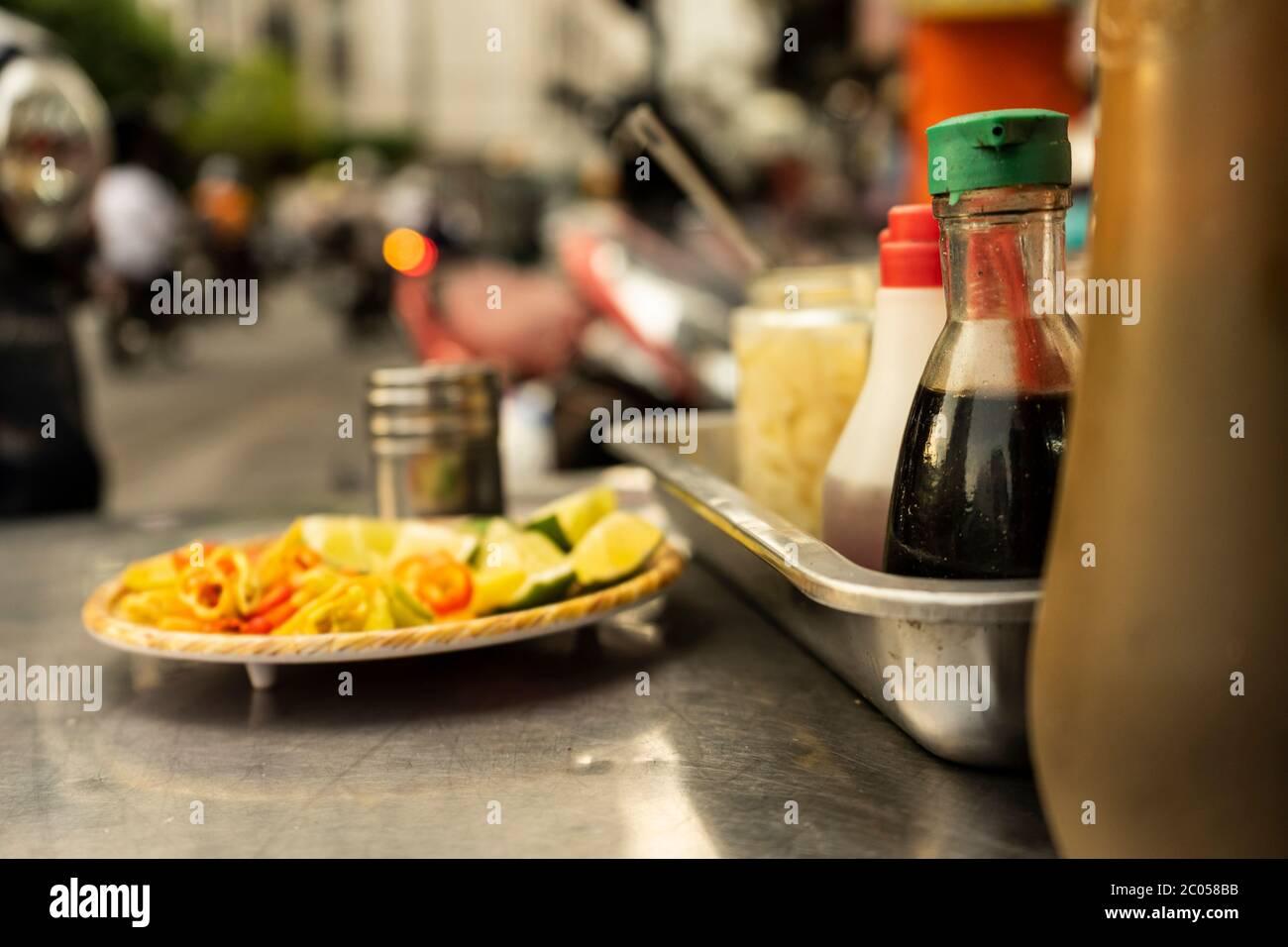 Bandeja de condimentos de fideos vietnamitas tradicionales con un plato de rodajas de limón, tarro de Chile, salsa de pescado, salsa de soja, cucharas y palillos en el carrito de comida callejera Foto de stock