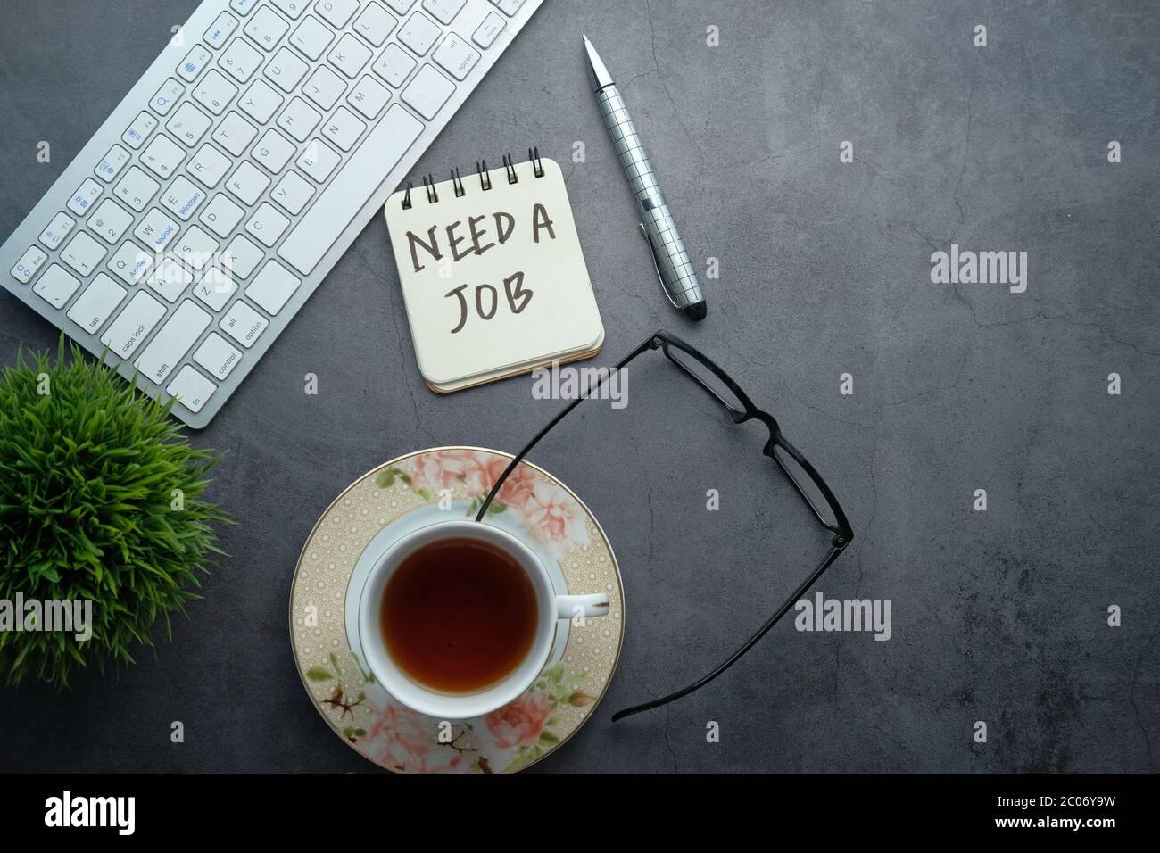 Necesita un trabajo, buscando. Texto en el escritorio de la oficina con espacio para copias. Foto de stock