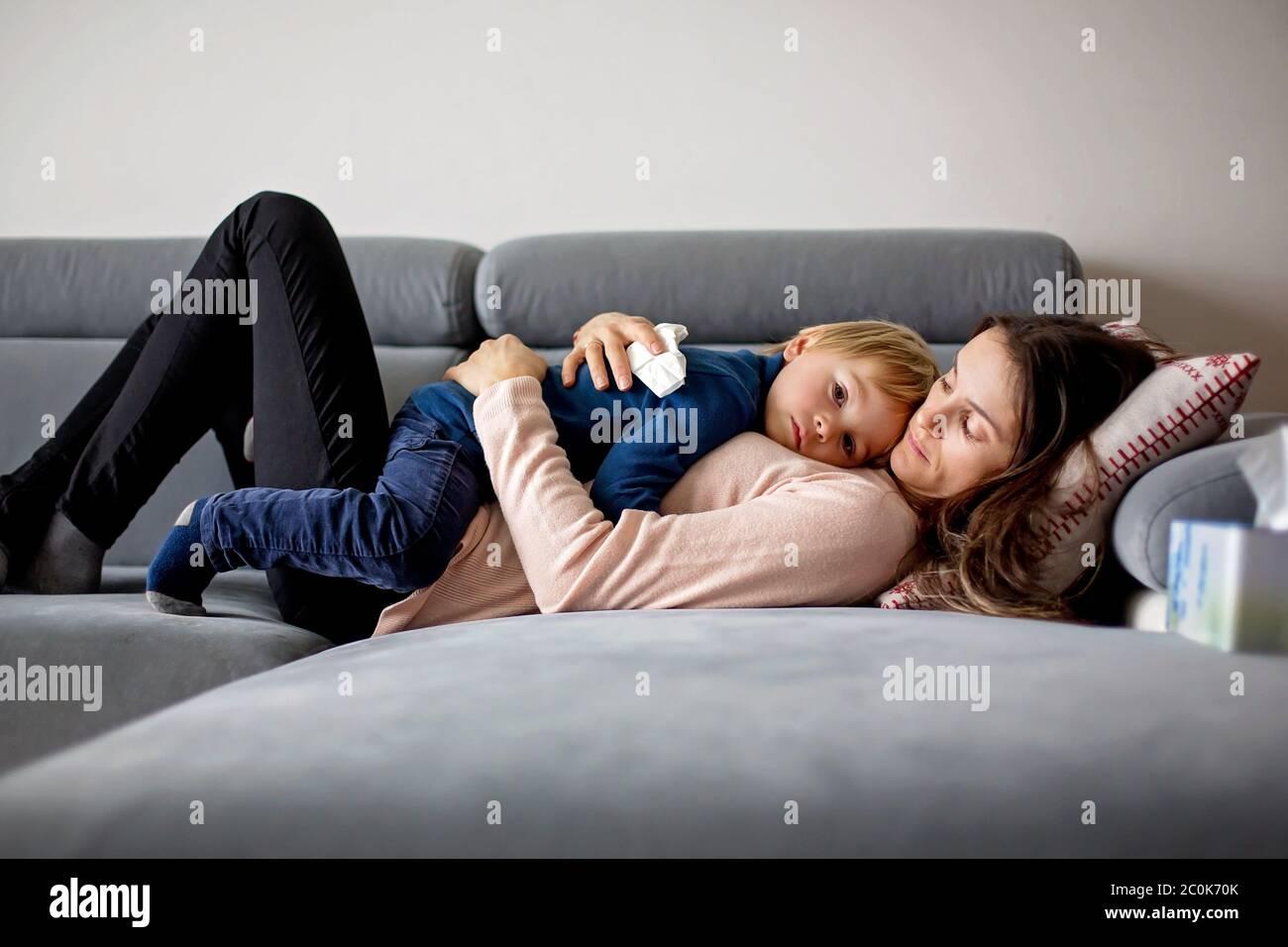 Madre que sostiene a un niño enfermo, acostado en un sofá en casa con fiebre, nariz corriendo y temperatura, descansando Foto de stock