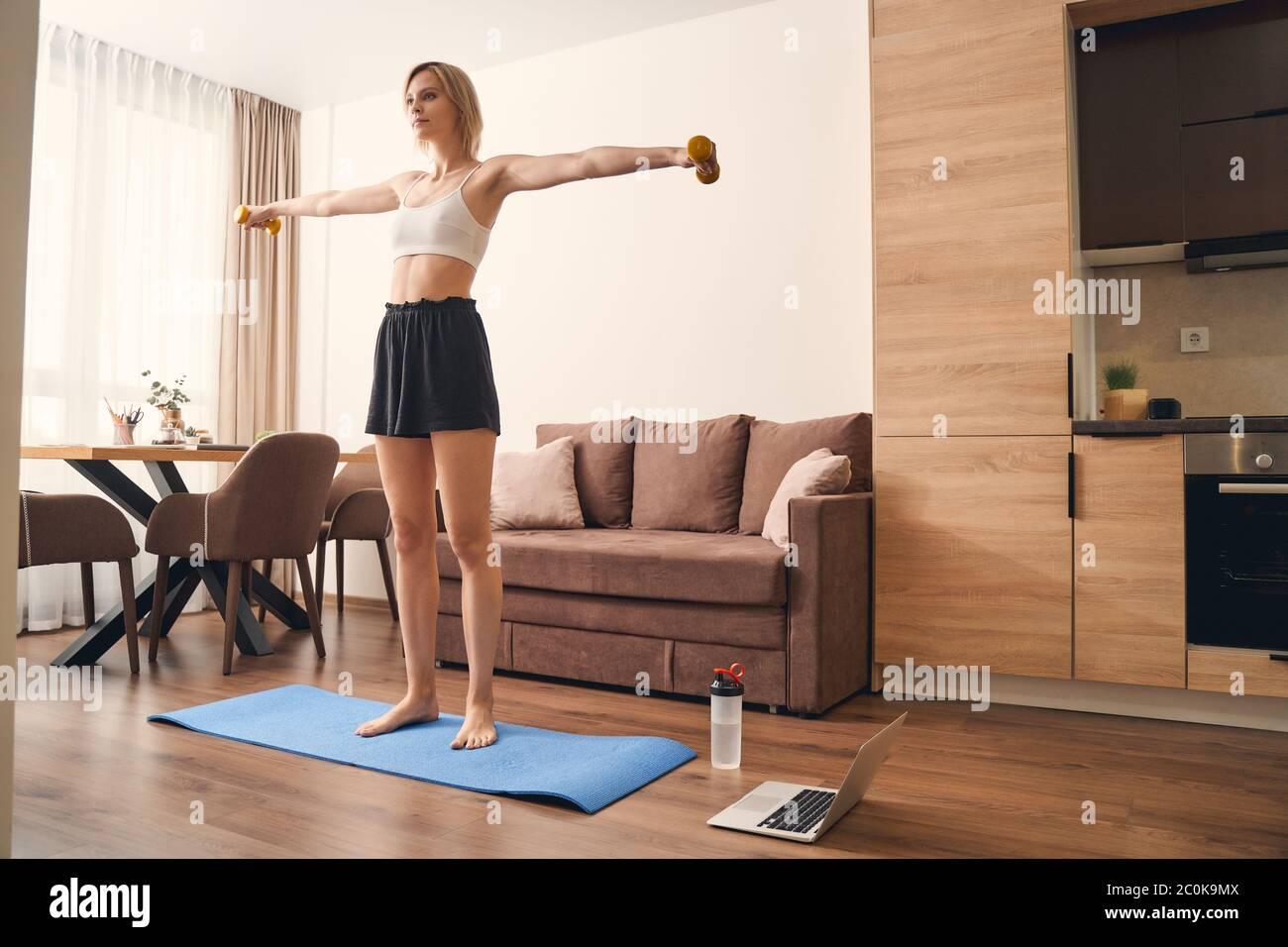 Ajuste a la señora haciendo un ejercicio con pesas Foto de stock
