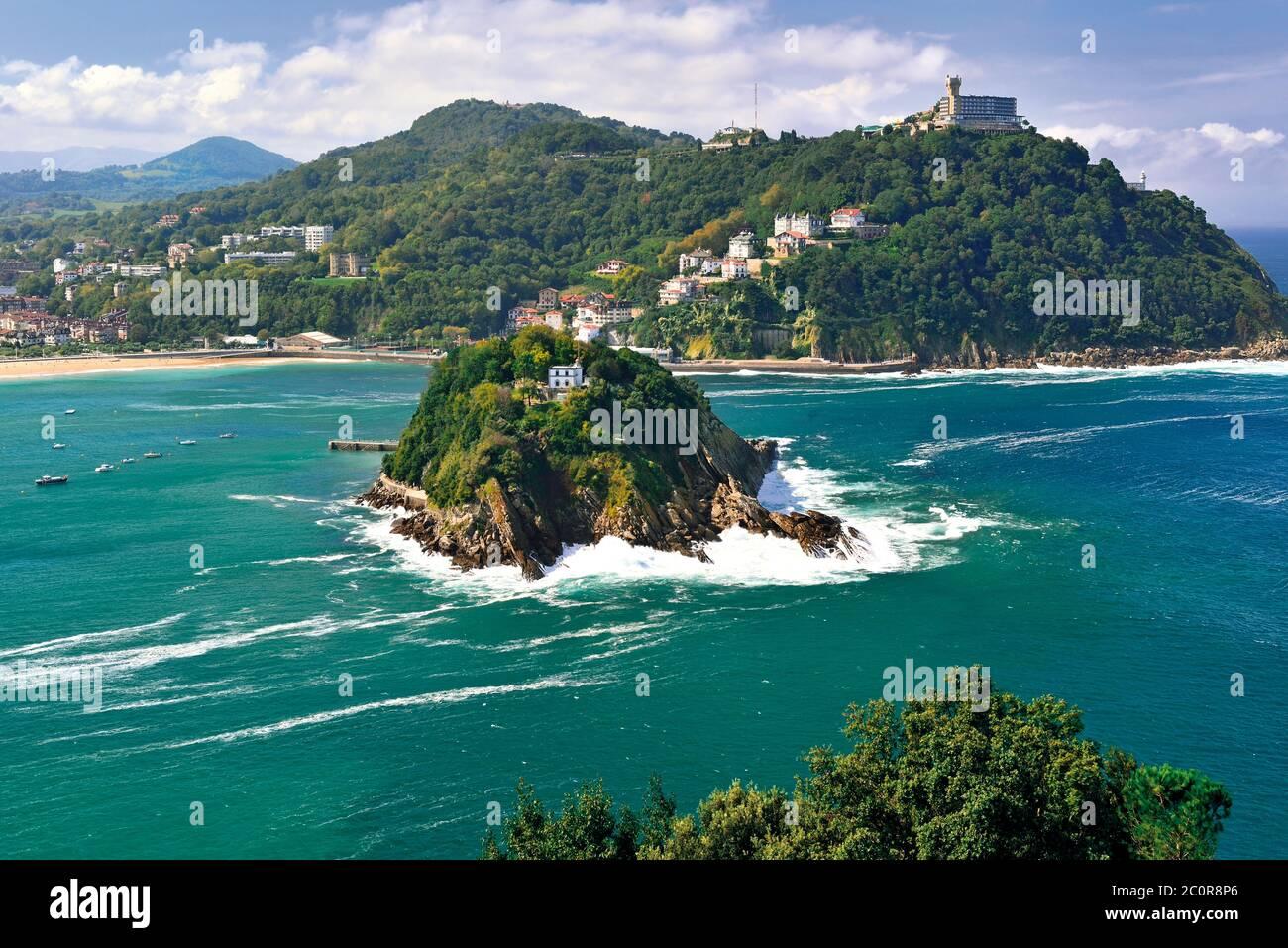 Vista a la pequeña isla verde en medio del océano verde y la colina con el edificio en la parte superior rodeado de playa de arena (San Sebastián) Foto de stock