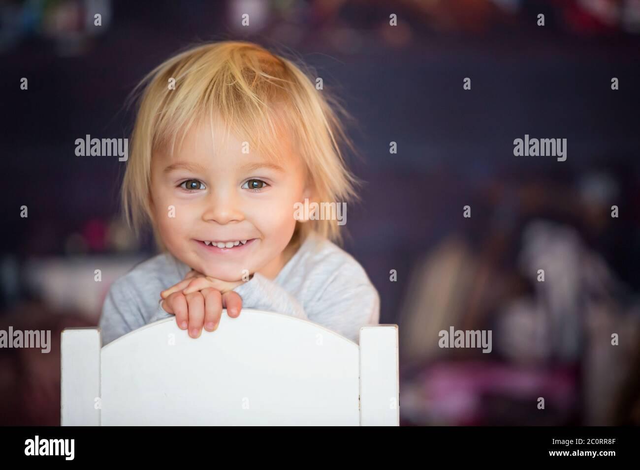 Hermoso niño rubio, sentado en una silla, jugando con juguetes en una sala de juegos Foto de stock