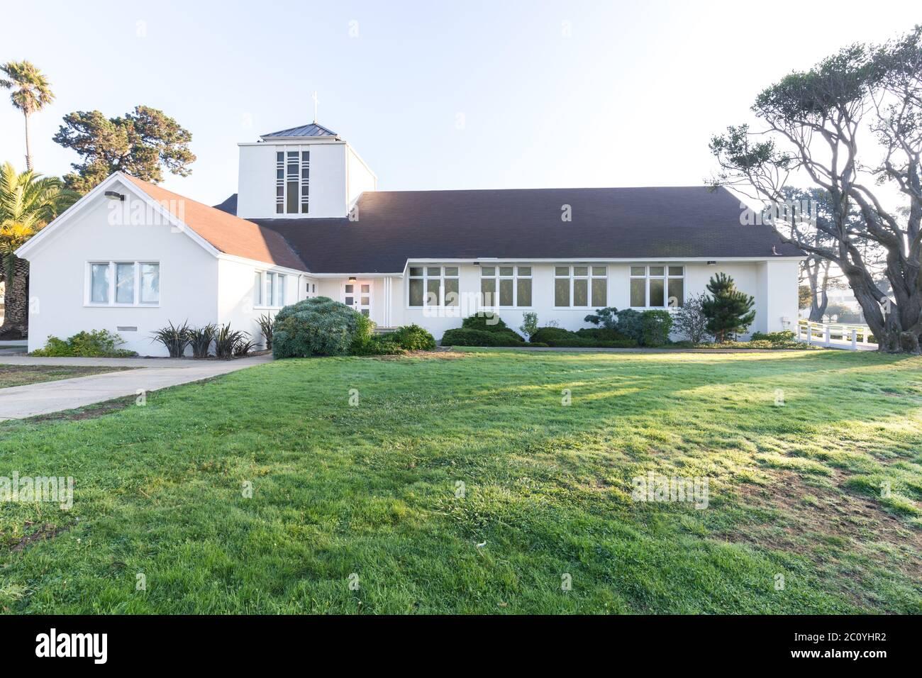 La casa de la iglesia y los prados con sunbeam Foto de stock