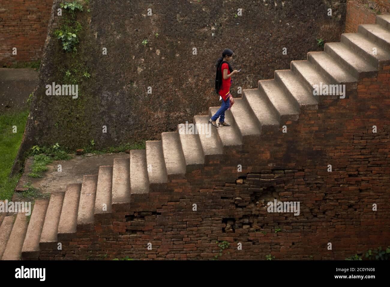 Una mujer que se acerca a la escalera del Monasterio 1 en el antiguo complejo universitario budista de Nalanda en Nalanda, Bihar, India. Foto de stock