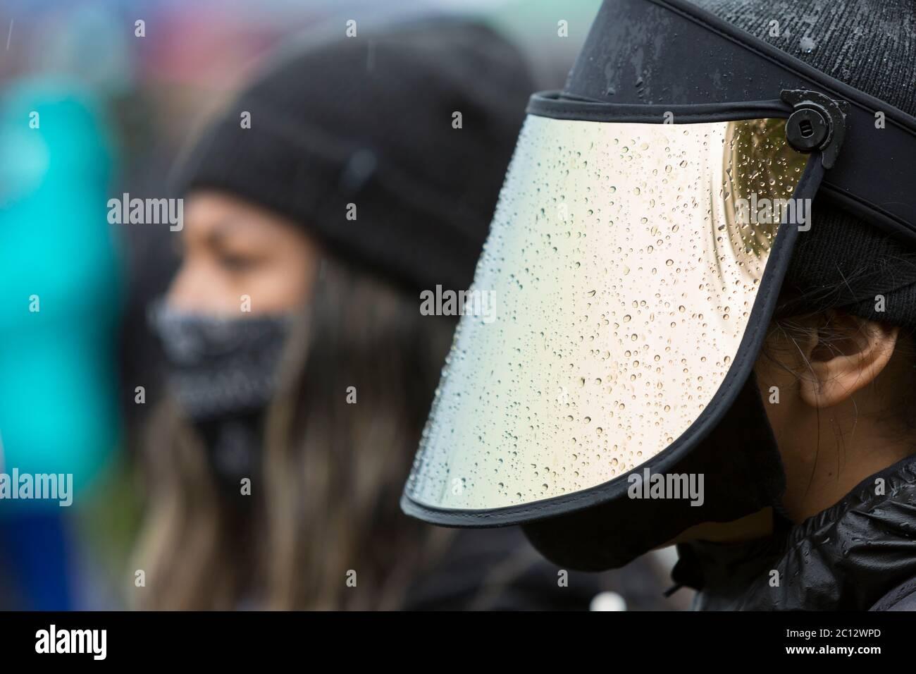 Un defensor de un escudo facial se enfrentaba a fuertes lluvias para asistir a la marcha silenciosa a nivel estatal y a la huelga general en el Parque Judkins en el barrio del Distrito Central de Seattle el viernes, 12 de junio de 2020. Black Lives Matter Seattle-King County organizó el día de acción y la marcha silenciosa a nivel estatal para honrar las vidas perdidas en apoyo de todas las vidas negras en el estado de Washington. Foto de stock