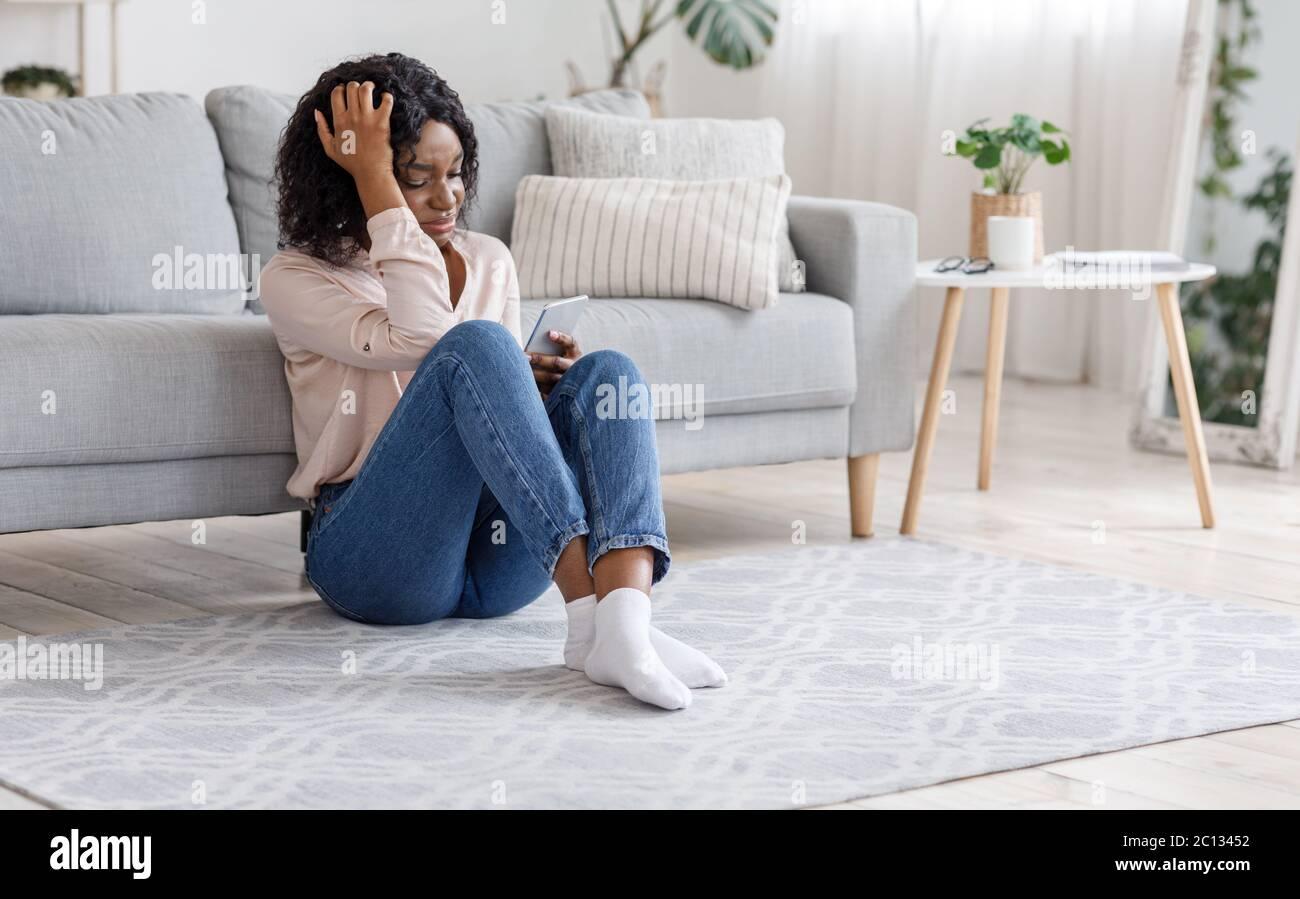 Chica desgarrada. Llorando Mujer Negra sentada con un smartphone en el piso de casa Foto de stock