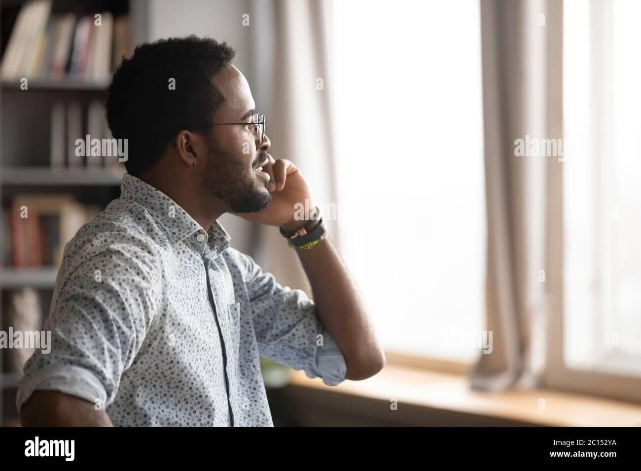 Un hombre de negocios africano que sostiene el teléfono móvil hablando resolver problemas a distancia Foto de stock