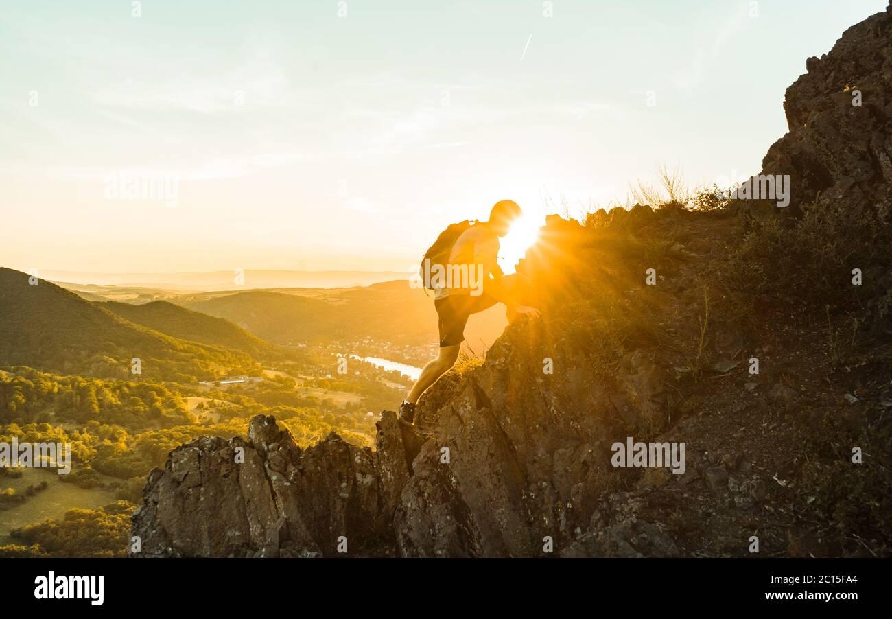 Viaje hombre turístico solo en las montañas de los acantilados y mirando en el valle. Silueta de la persona en la roca alta al atardecer. Aventura de senderismo Foto de stock