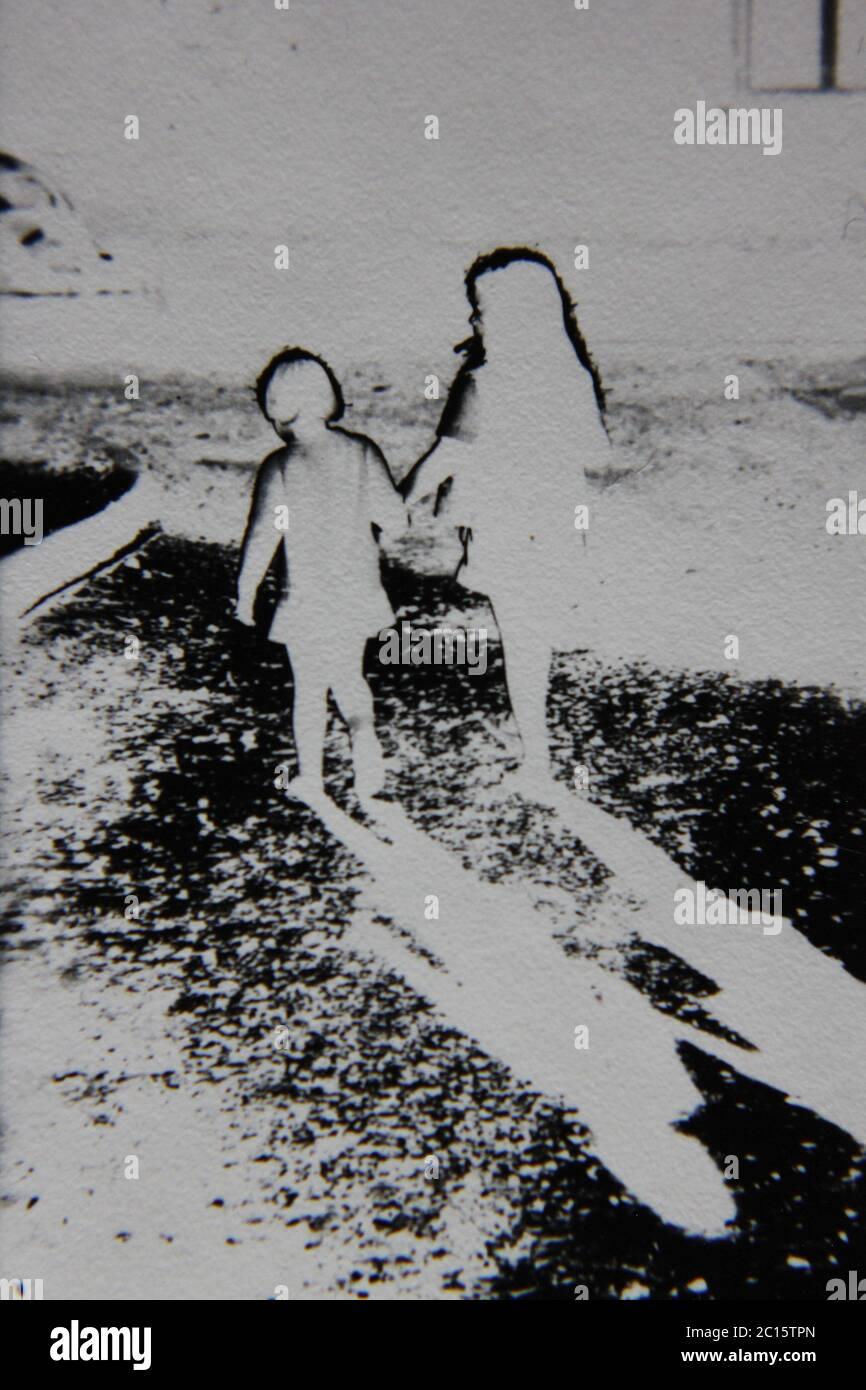 Fotografía extrema en blanco y negro de la cosecha de los 70 de dos chicas que caminan lejos de la cámara. Foto de stock