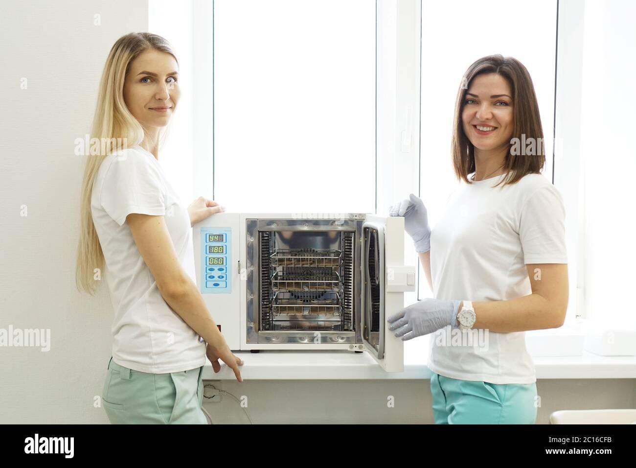 Calor seco para instrumentos de esterilización. Dos mujeres amigas - maestras de un salón de belleza Foto de stock