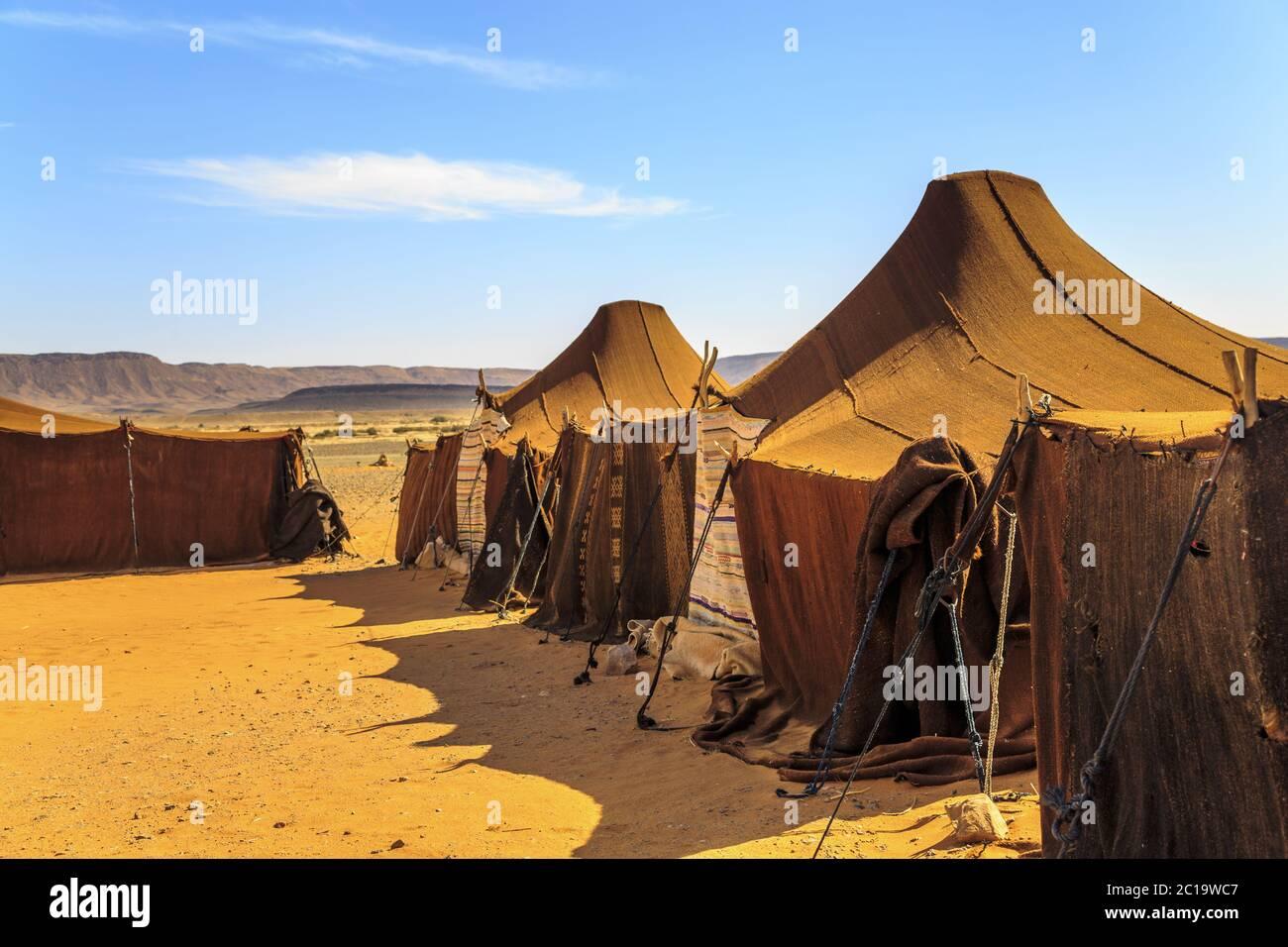 Tiendas en medio del desierto con montañas en el fondo, en un día soleado Foto de stock