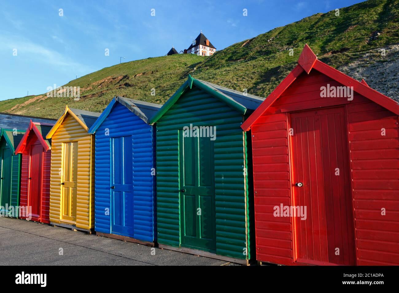 Coloridas cabañas de playa bajo el paseo marítimo del norte, Whitby, Yorkshire del Norte, Inglaterra, Reino Unido, Europa Foto de stock