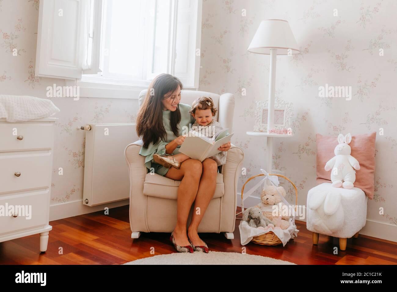 niña que se divierte sentada sobre su madre embarazada en la habitación Foto de stock