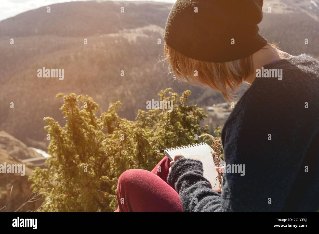 Retrato de una hipo chica con gafas de sol y un sombrero sentado en una roca al aire libre en las montañas contra un cielo azul. Independiente Foto de stock
