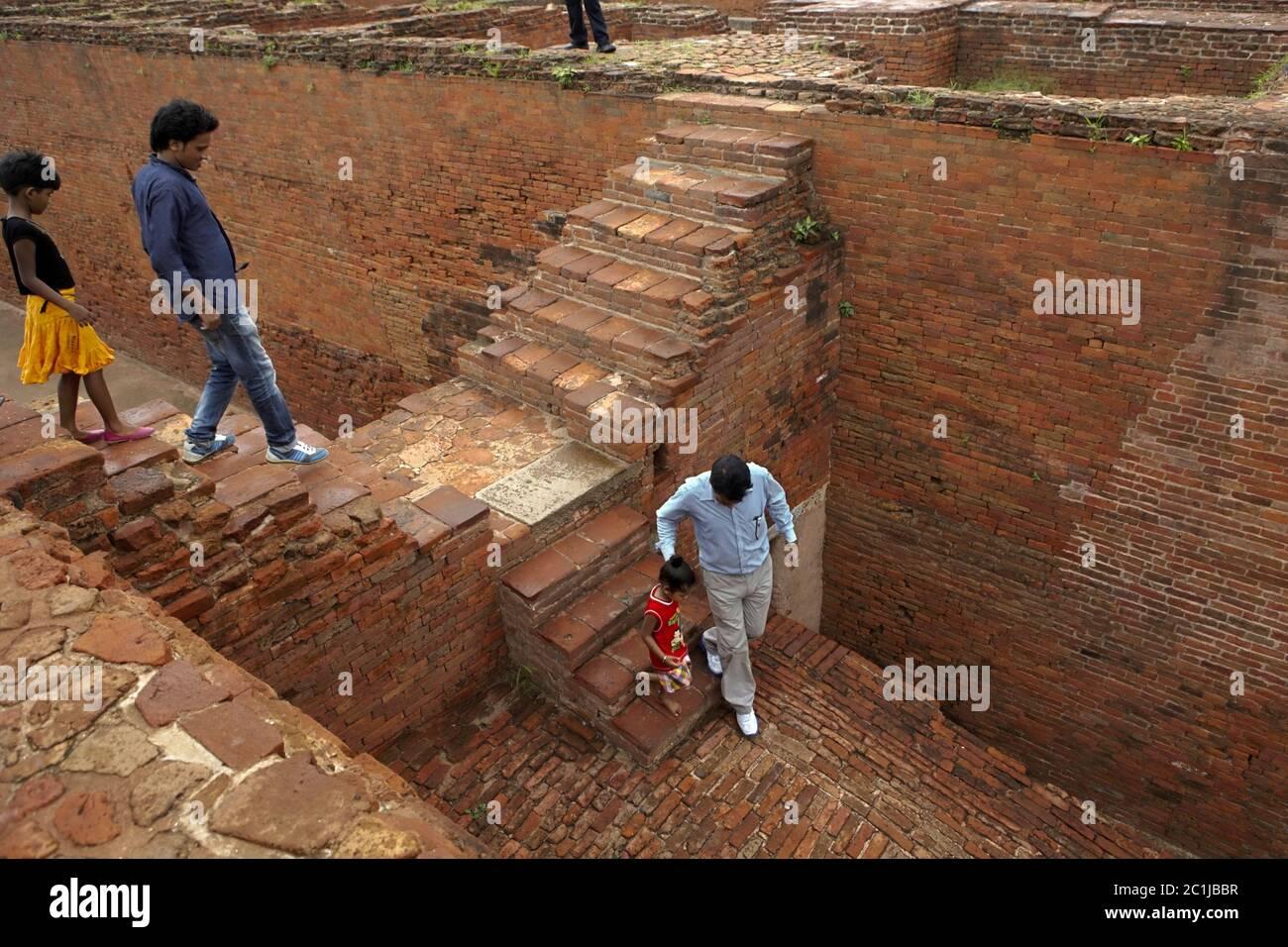 Familia que desciende de uno de los monasterios excavados dentro del antiguo complejo universitario budista Nalanda en Nalanda, Bihar, India. Foto de stock