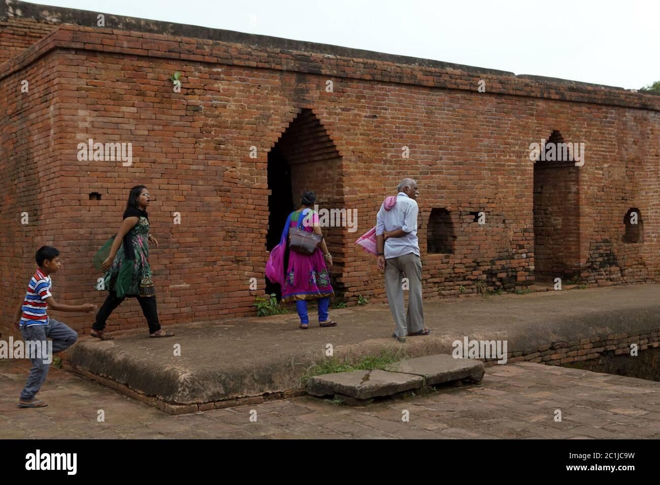 Un guía y una visita familiar local a uno de los monasterios excavados dentro del antiguo complejo universitario budista de Nalanda en Bihar, India. Foto de stock