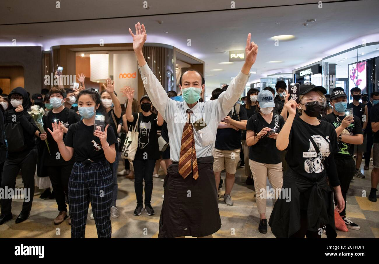 """HONG KONG,HONG KONG RAE,CHINA: 15 DE JUNIO DE 2020. Los manifestantes sostienen el cartel de mano """"5 exige no menos"""" en Pacific Place Mall en Admiralty Hong Kong. Están allí para conmemorar la muerte de los primeros manifestantes democráticos hace un año. Marco Leung cayó a su muerte por andamios fuera del edificio el 15 de junio de 2019. Se le conoció como el hombre impermeable. Imagen de stock de Alamy/Jayne Russell Foto de stock"""