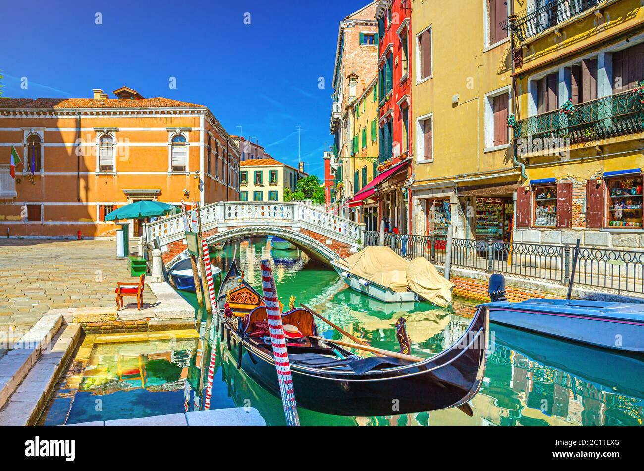 Paisaje urbano de Venecia con góndola y lanchas a motor amarradas en el estrecho canal de agua Río dei Frari, edificios coloridos y puente de piedra, región del Véneto, norte de Italia, fondo azul cielo en el día de verano Foto de stock