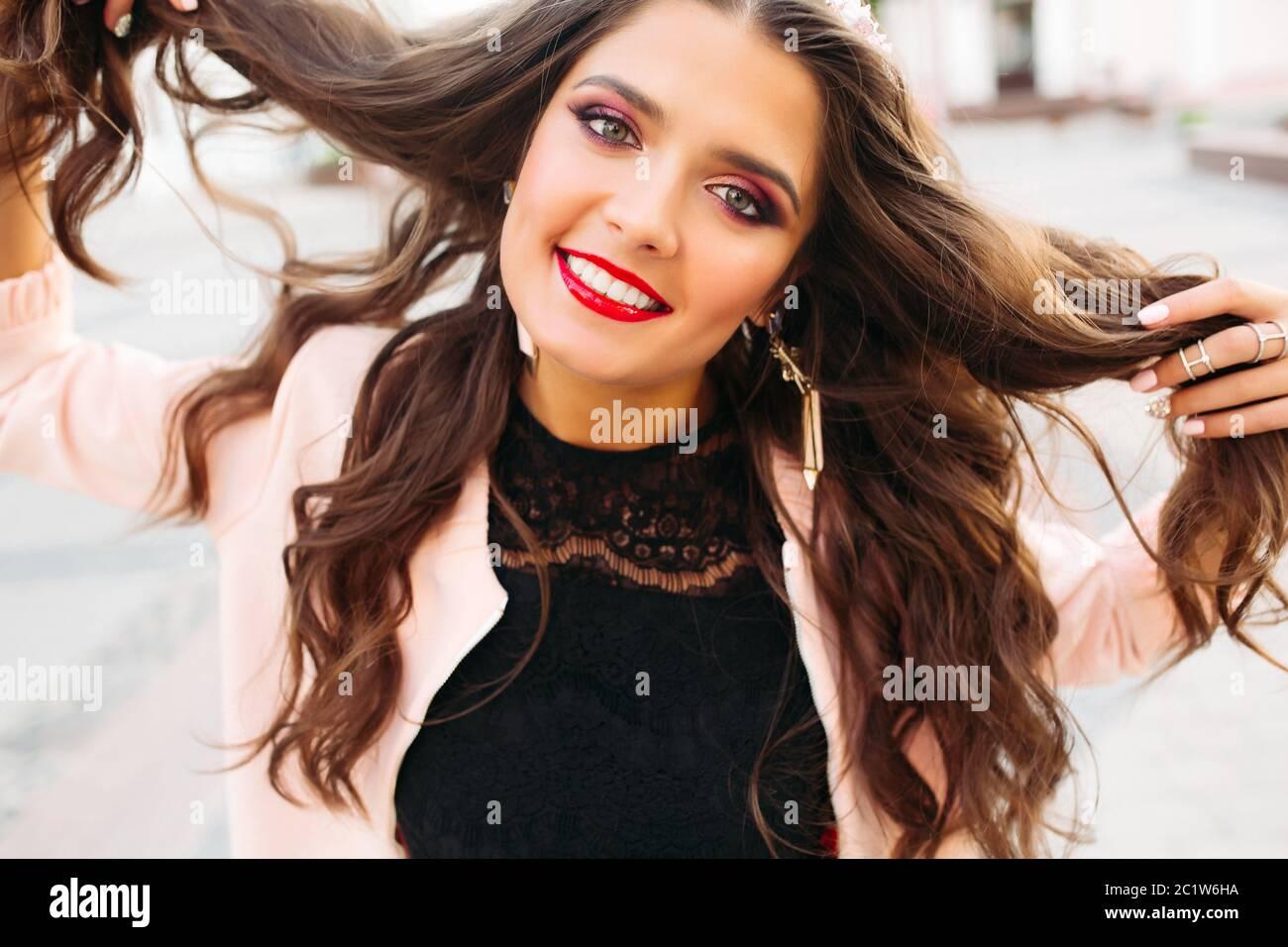 Hermosa morenita chica con brillantes componen sosteniendo su cabello y sonriendo a la cámara. Foto de stock