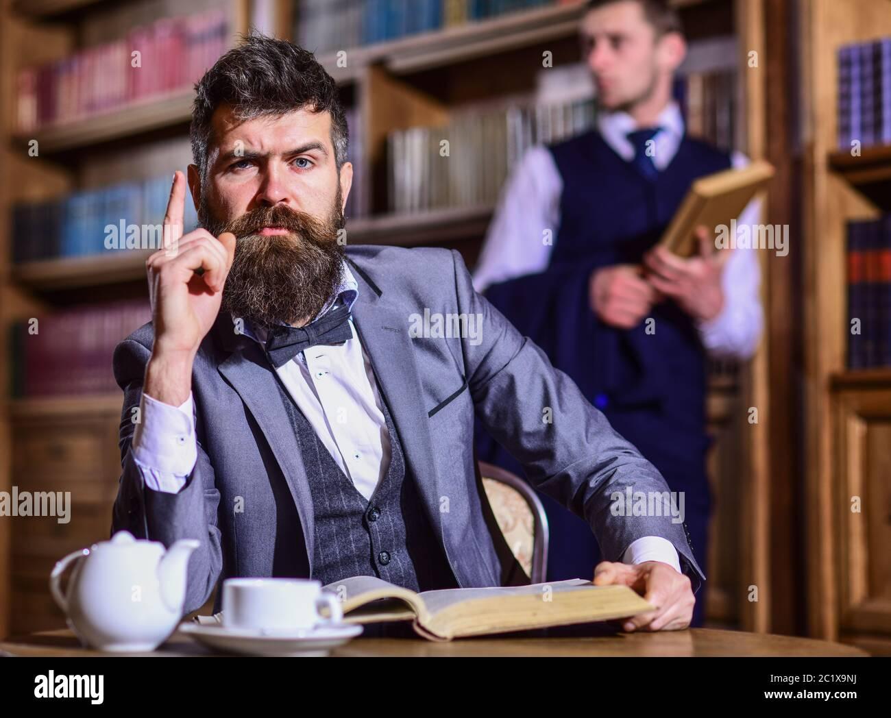 Detectives retro trabajan en investigación en sala antigua. Hombres en traje, detectives pasar el ocio en la biblioteca. Concepto de investigador y detective privado. Hombre con barba y cara estricta descubrió acertijo. Foto de stock