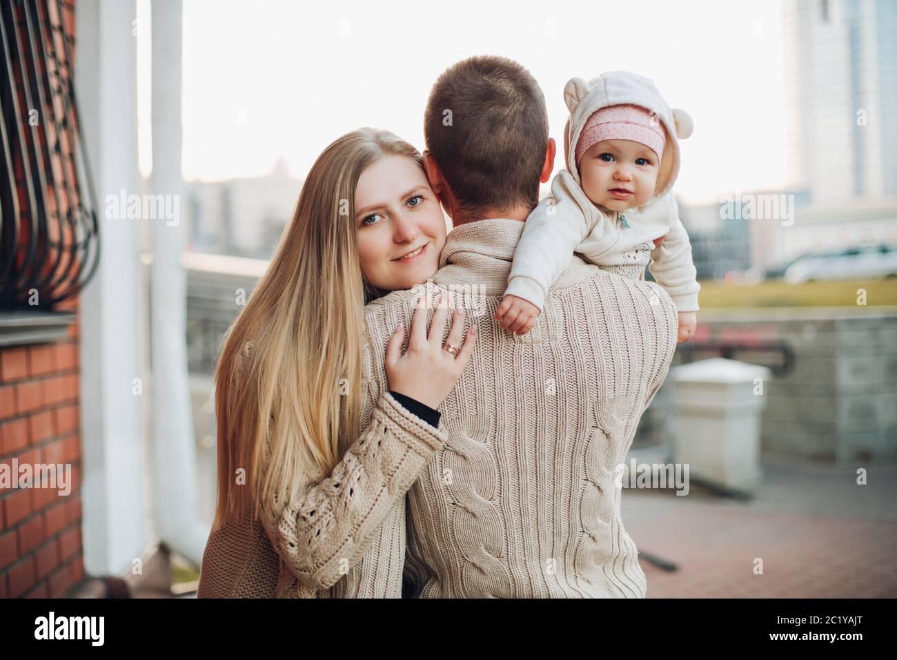 Joven familia feliz sonriendo ante la cámara y juntos. Foto de stock