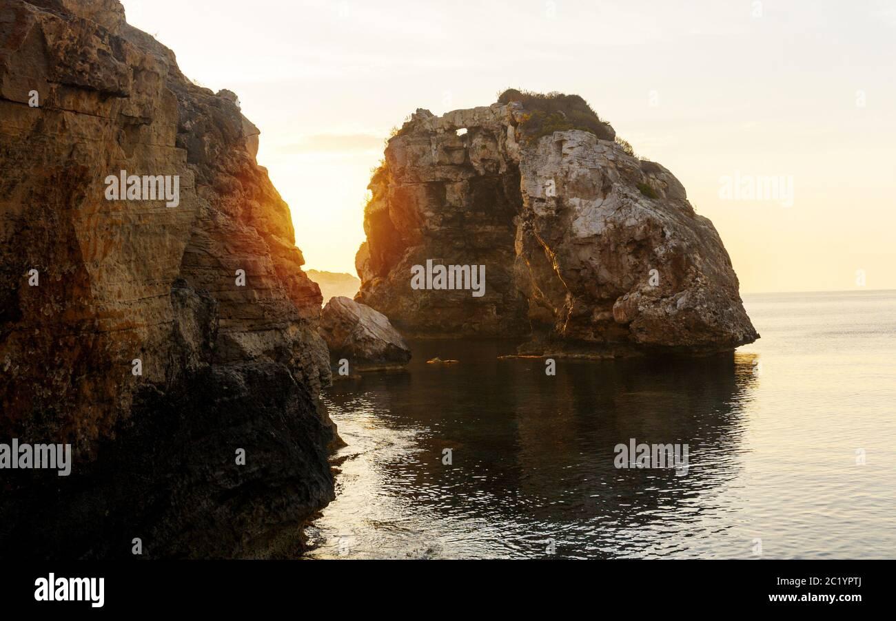 Es Pontas en Mallorca con barco anclado cerca en el mar Mediterráneo. Amanecer con yate y arco de roca cerca de Santanyí Mallorca. Foto de stock