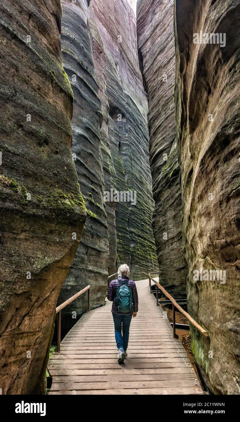 Mujer mayor hiker dentro del cañón de ranura en las rocas de Adrspach, Reserva Natural Nacional de las rocas de Adrspach-Teplice, Sudetes centrales, República Checa Foto de stock