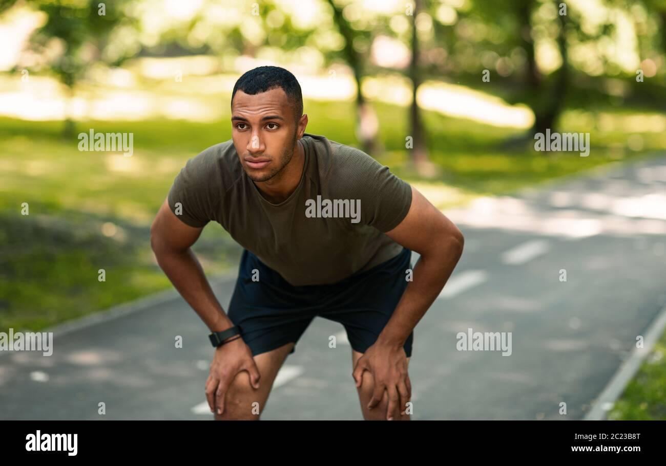 Joven corredor afroamericano tomando descanso después de su entrenamiento en el parque Foto de stock