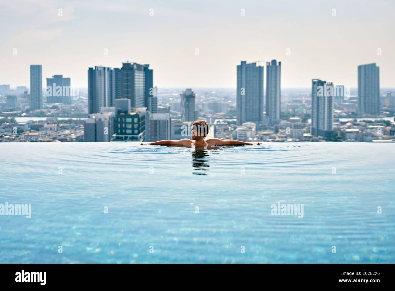 Un joven se relaja en el borde de la piscina en la azotea del hotel Foto de stock