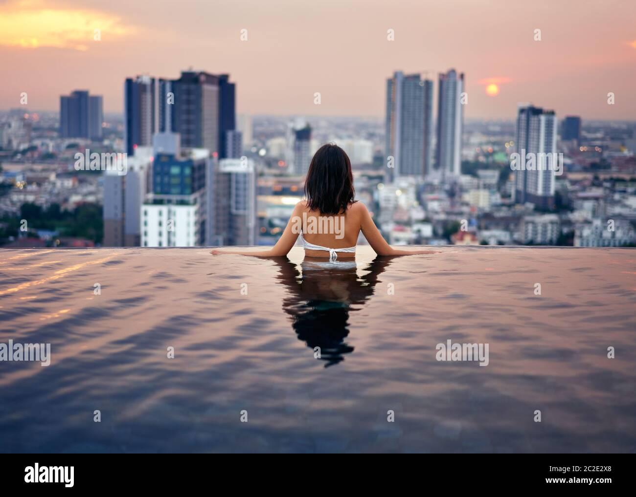 Mujer joven relajarse en la piscina en la azotea durante la puesta de sol increíble y disfrutar de la vista de la ciudad Foto de stock