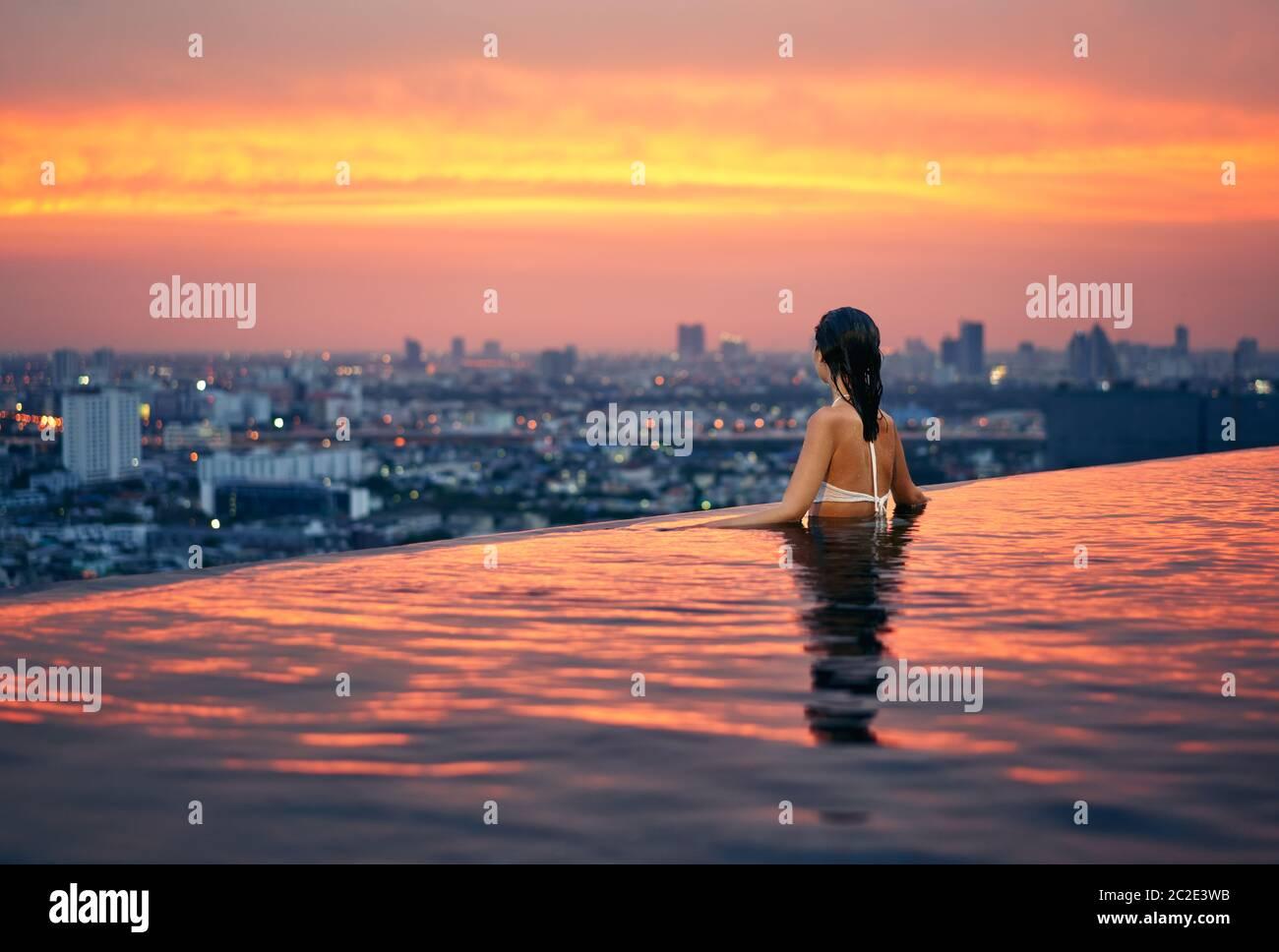 Una joven se relaja en la piscina en la azotea durante una increíble puesta de sol y disfruta del paisaje urbano Foto de stock