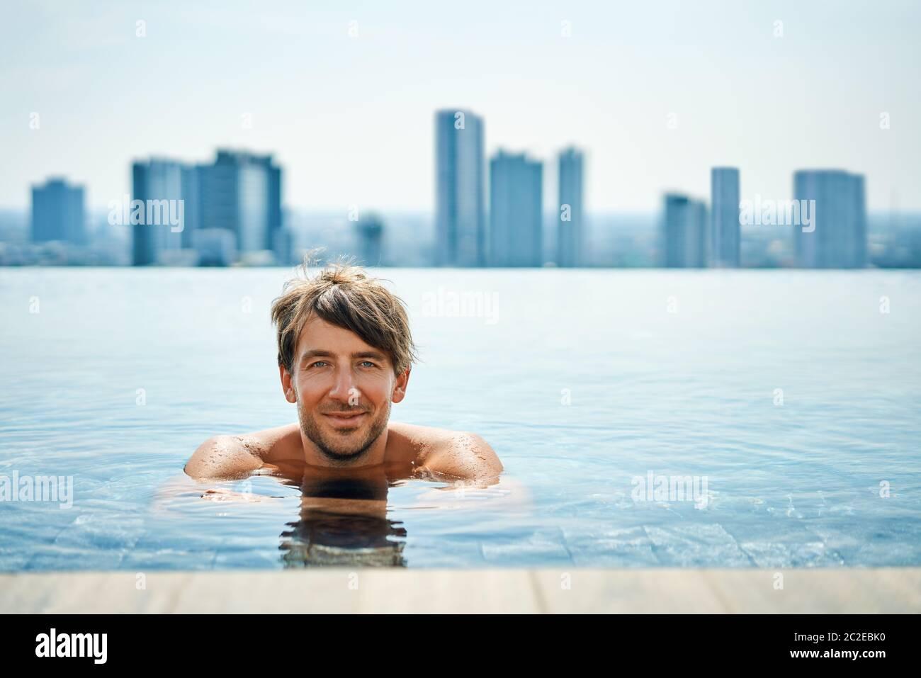 Hombre guapo Relájate en la piscina Foto de stock