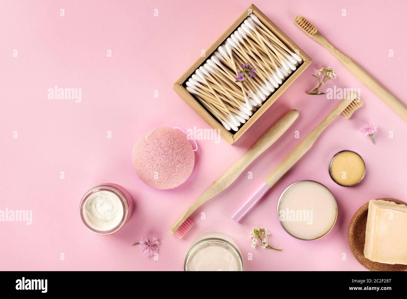 Cosméticos sin plástico, sin residuos, planos sobre un fondo rosa. Cepillos de dientes de bambú y hisopos de algodón, esponja konjac, natural Foto de stock